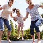 Granny, mom and daughter jumping on trampoline